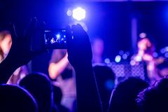 people taking photographs with touch smart phone during a music concert - stock photo