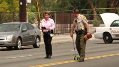 Officer using surveryor's wheel at crime scene Stock Footage