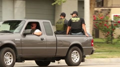 Swat officers riding the back of pickup truck Stock Footage