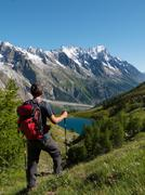 hiker admiring mountain landscape in val veny, mont blanc - stock photo
