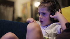 Little boy watching tv and wearing headphones, closeup, steadycam shot Stock Footage