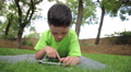 little beautiful boy plays the tablet in the park HD Footage