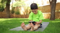 little beautiful boy plays the tablet in the park, dolly 2 Footage