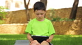 little boy plays the tablet in the park, dolly 5 HD Footage