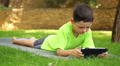 little boy plays the tablet in the park, dolly 4 Footage