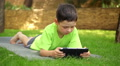 little boy plays the tablet in the park, dolly 2 Footage