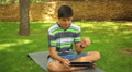 handsome teenager playing tablet in the park Footage