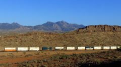 Distant Train Rolling Through Kingman AZ With Mountain Background Stock Footage