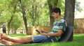 handsome teenager playing tablet in the park, dolly 2 Footage