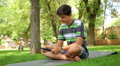 handsome teenager playing tablet in the park, dolly 1 HD Footage