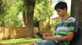 teenager plays the tablet in the park, dolly 5 HD Footage