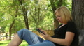 beautiful blonde plays in a small tablet in the park, dolly 8 Footage