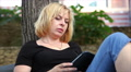 beautiful blonde plays in a small tablet in the park HD Footage