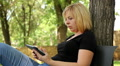 beautiful blonde plays in a small tablet in the park, dolly 6 Footage