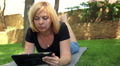 beautiful woman playing on tablet in the park, dolly 4 Footage
