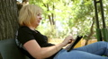 beautiful woman playing on tablet in the park, dolly 2 Footage