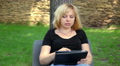beautiful woman playing on tablet in the park, dolly 1 Footage