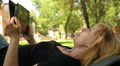 beautiful blonde listens to music on a tablet in the park HD Footage