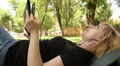 beautiful blonde listens to music on a tablet in the park, dolly 3 HD Footage