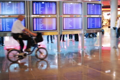 Departure boards, international airport and man riding on bike Stock Footage