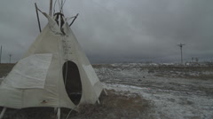 Indian Reservation tipi pan to church during wind storm Stock Footage