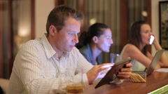 Busy man using tablet in pub at night Stock Footage