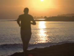 Man jogging on footway at sunrise, steadycam shot, slow motion shot Stock Footage