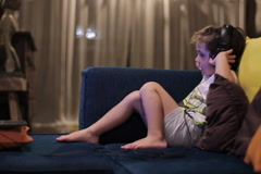 Boy sitting on sofa and looking on laptop, steadycam shot Stock Footage