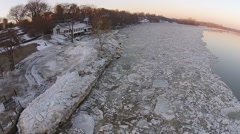 Flying over ice in River at Sunrise Stock Footage