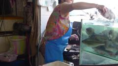 Woman catches live flopping fish from the water,lets the customer make a choice Stock Footage