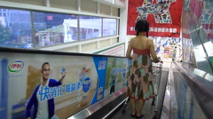 Woman with shopping cart on the elevator goes down to the supermarket Stock Footage