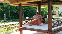 Couple lying on bed in exotic garden and reading Stock Footage