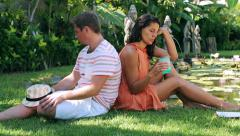 Bored Couple sitting on the grass in exotic garden  Stock Footage