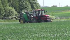 Tractor spraying wheat field with sprayer, herbicides and fertilizer Stock Footage