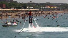 Man on Water Jet Pack Flyboard near Sea Beach Resorta ans people Crowd Stock Footage