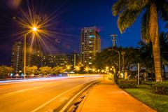 palm trees and buildings along dade boulevard at night, in miami beach, flori - stock photo