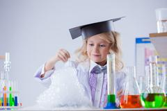 Smiling cute chemist watching chemical reaction - stock photo