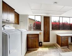Bright laundry room with dark brown cabinets Stock Photos
