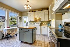 Kitchen interior in old house with island and antique table Stock Photos