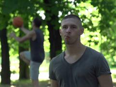 Man eating apple on baskeball court in park, super slow motion, 240fps NTSC Stock Footage
