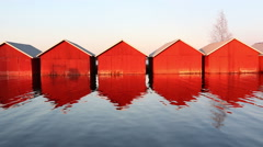 Red wooden boathouses with water waving lightly - stock footage
