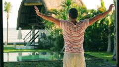 Man going to his exotic backyard, steadycam shot Stock Footage