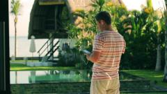 Man listening music on cellphone in exotic place, steadycam shot Stock Footage