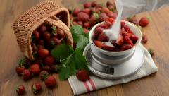 Filling sugar over strawberries on weight scale Stock Footage