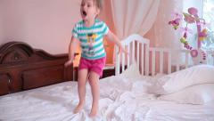 Cheerful little cutie jumping on a bed.  Time lapse. - stock footage