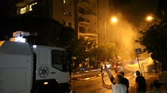 Police use water cannon to disperse violent demonstrators Stock Footage