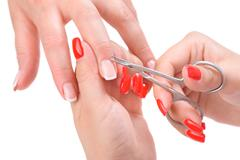 manicure applying - cutting the cuticle - stock photo
