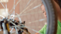 Little boy repairing a bicycle, he tightens the nuts and bolts Stock Footage