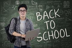 handsome student holds laptop in class - stock illustration