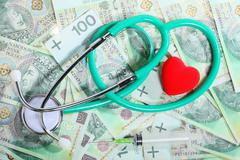 Stock Photo of cost of health care: stethoscope red heart polish money
